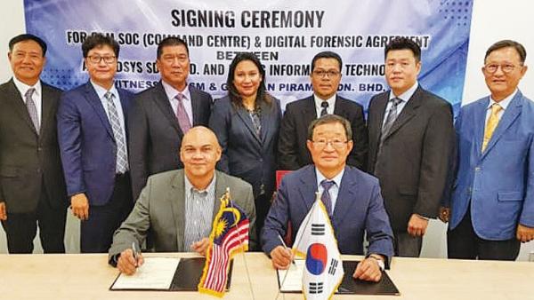 이명재 명정보기술 대표(앞줄 오른쪽)와 말레이시아 사이버보안청 보안관제센터 구축업체 아센시스의 모하메드 시합 대표가 7월 24일 협약서에 서명하고 있다.